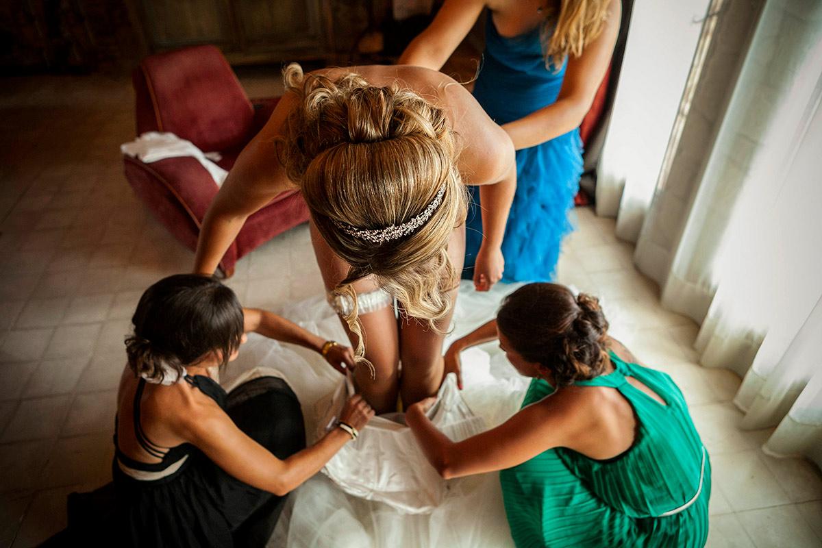 la nuvia amb les dames d´honor ajuden a posar se el vestit al castell d´empordà