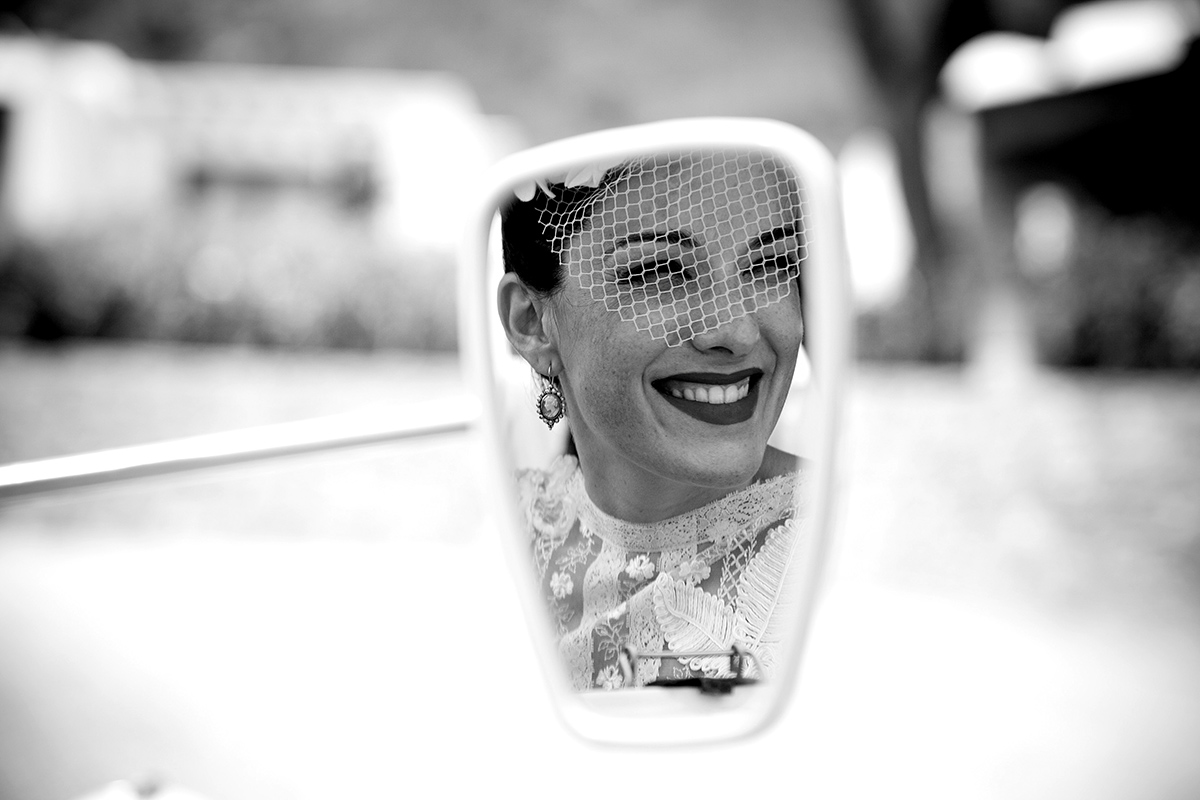 la nuvia es reflexa al mirall del coche abans d´entrar a la cerimonia
