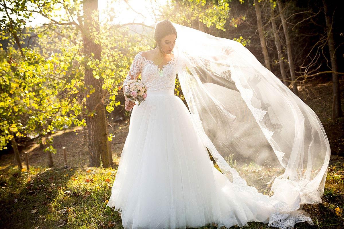 nuvia jugant amb el vel del vestit amb una llum de tardor