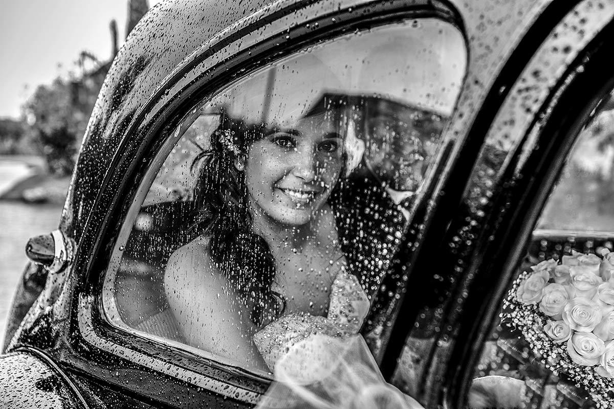 la nuvia arriba amb el coche nupcial en un dia de pluja amb el seu marit al restaurant Siloc