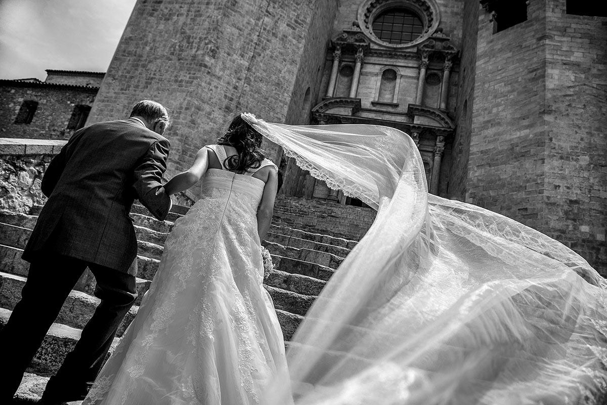 la nuvia i el seu pare pugen les escales de la catedral cap a la cerimonia
