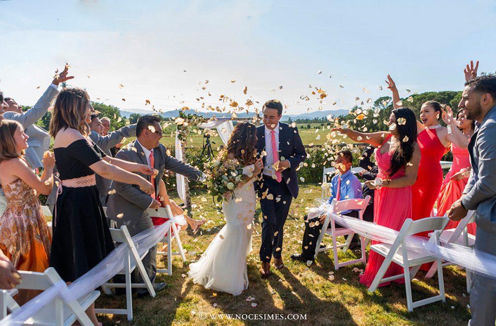 els convidats tiren petals de flors als nuvis casats