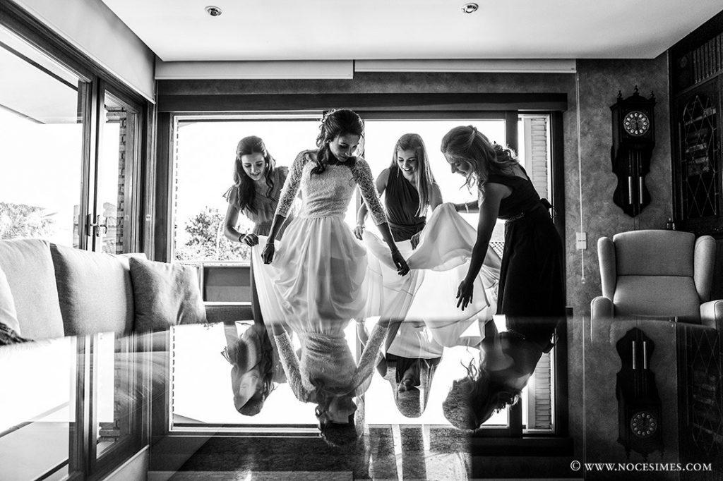 les germanes ajuden a posar el vestit de la nuvia