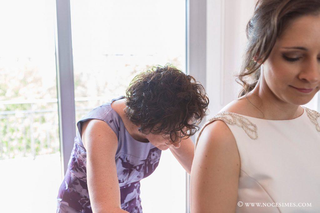 la mare ajuda amb el vestit a la nuvia