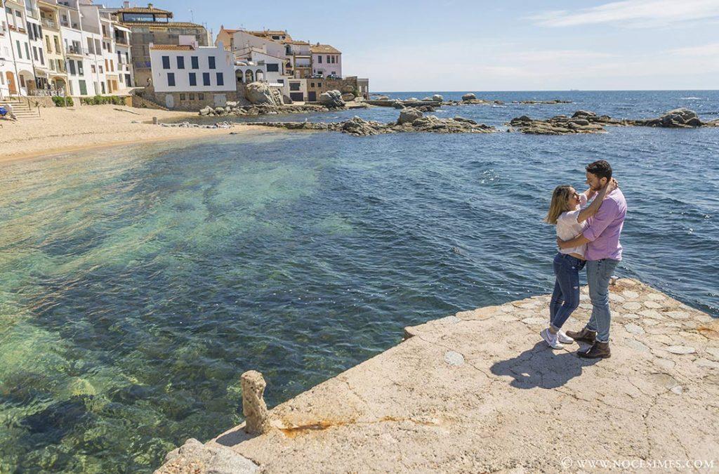 parella abraçada davant la platja de port bo